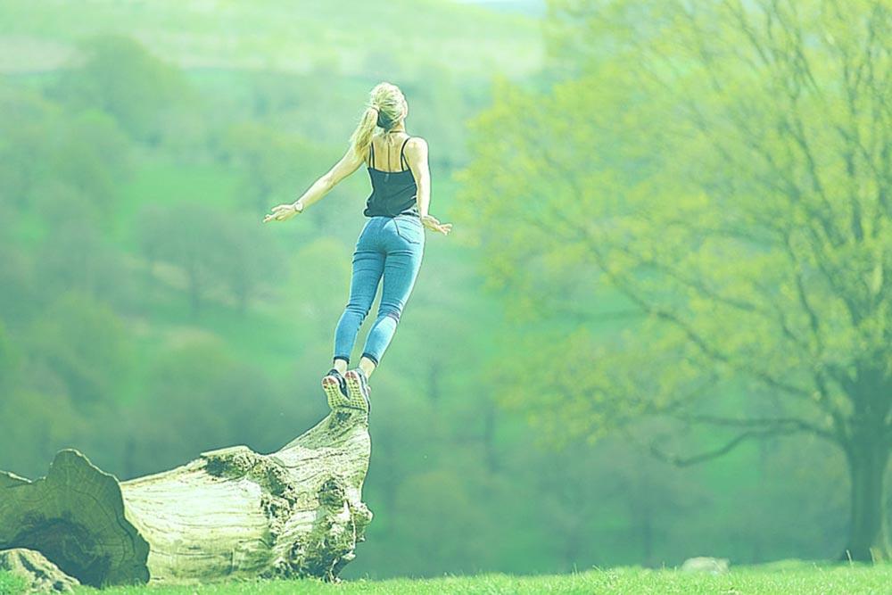 Motivierte, sportliche Frau streckt sich auf einem Baumstamm in der Natur
