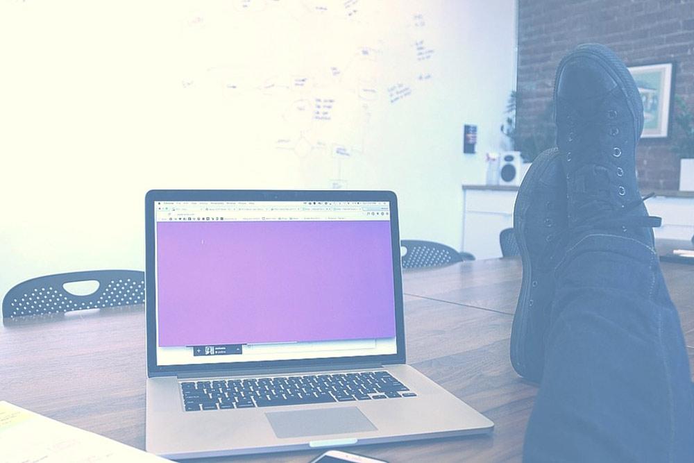 Mensch am Schreibtisch, Notebook aufgeklappt, Füße hochgelegt und Notizen an der Wand
